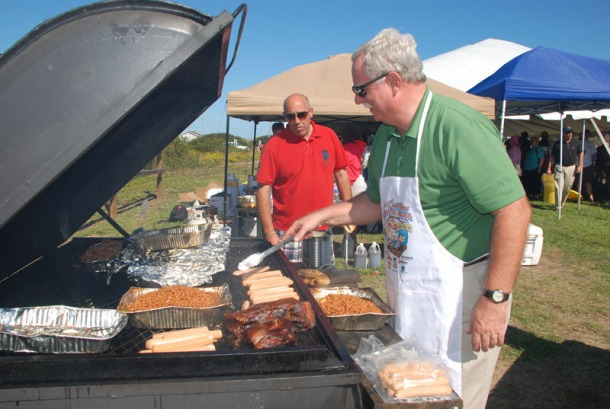 First Flight Rotary club members Mark Cutlet and Warren Wrenn cooked the pig at the 2011 Oink N' Oyster Roast. (photo: RIFP)