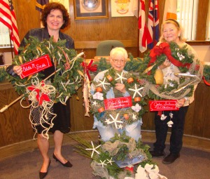 Shown is Kim Sawyer (left), Executive Director of Roanoke Island Festival, who judged the competition - an honor given to last years winner - holding the first place winner, Odds and Ends; Roanoke Island Garden Club member Jerri Hopkins (seated), a former downtown merchant, displaying the two who tied for third place - Poor Richard's Sandwich Shop and Acre Lane; and Roanoke Island Garden Club member and project organizer, Della Basnight, showcasing the second place winner, John Silver Art Gallery.