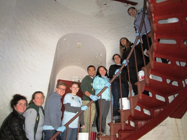 """University of Vermont students inside the Cape Hatteras Lighthouse performing """"spring cleaning"""" tasks."""
